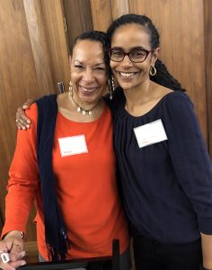 Dr. Cheryl Grills and Nkem Ndefo smiling with arms around each other.